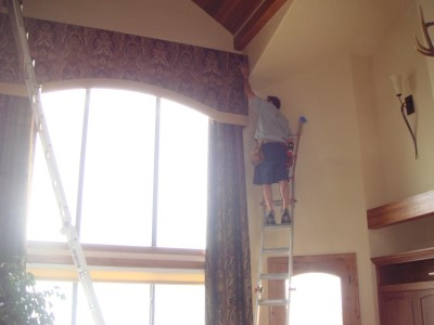 Picture of man up on ladder hanging cornice
